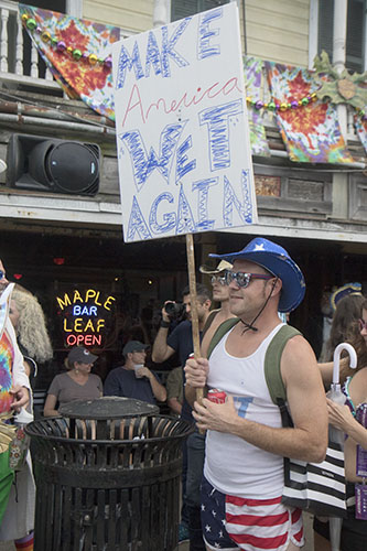 "Dustin Cook holds up a ""Make America Wet Again"" sign outside of the Maple Leaf Bar. The Krewe of O.A.K. celebrated the 30th anniversary of Mid Summer Mardi Gras with the theme ""Get Wet"". (Zach Brien, UptownMessenger.com)"