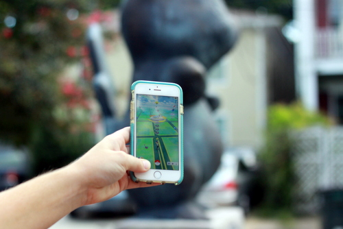 Madeline Dickson checks out the Pokemon gym at the Pikachu statue on her phone. (Robert Morris, UptownMessenger.com)