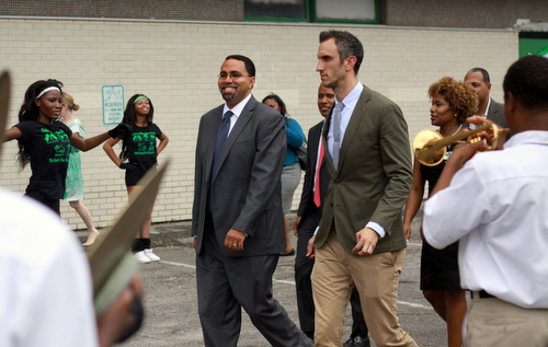 U.S. Secretary of Education John King is greeted by the band as he walks into Walter L. Cohen College Prep High School with principal Michael George. (Robert Morris, UptownMessenger.com)