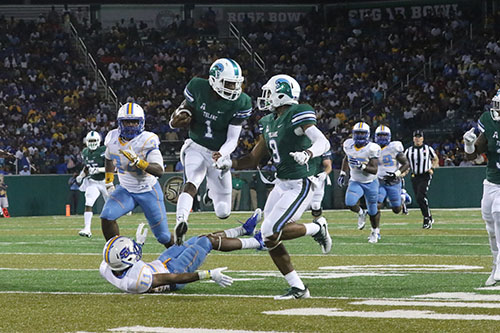 Tulane quarterback Johnathon Brantley hurdles a Southern defender on a lengthy run in the second quarter. Tulane defeated Southern University 66 to 21 at their home opener at Yulman Stadium. (Zach Brien, UptownMessenger.com)