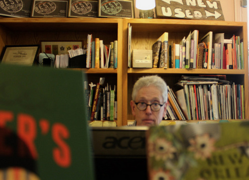 Gladin Scott looks up behind a pile of books on Oct. 24, 2016. Behind him are sticky notes with numbers of frequent customers and authors that he has compiled from his years as owner. (Photo by Dannielle Garcia, Loyola Student News Service).